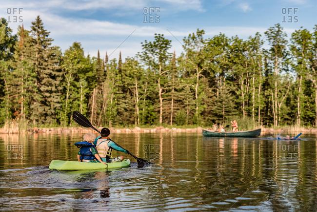 Kids riding in kayak on lake