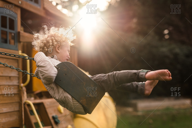 Boy with blonde curly hair on swing