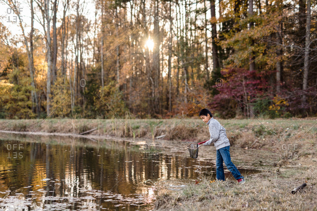 Boy fishing with a net on autumn lake