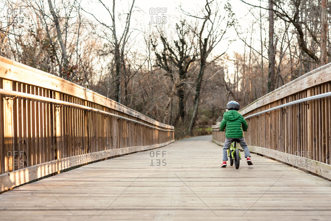 Boy riding bike on wood footbridge