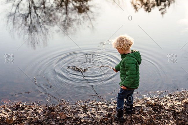 Boy touching pond water with stick