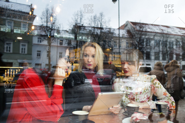 Young ladies with tablet at cafe