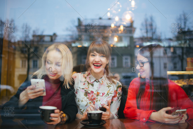 Laughing women with phones