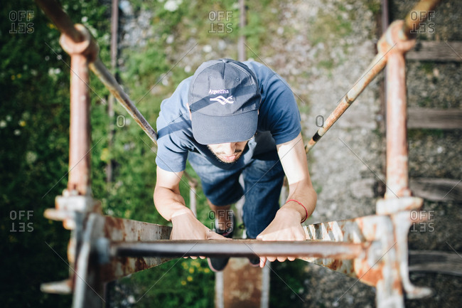 Man climbing up a wooden ladder in nature
