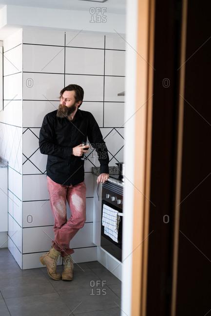 Bearded man drinking wine alone in kitchen
