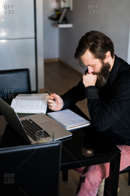 Man working at home with laptop and notebooks