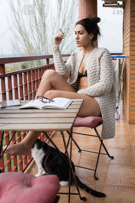 Female in lingerie and cardigan smoking