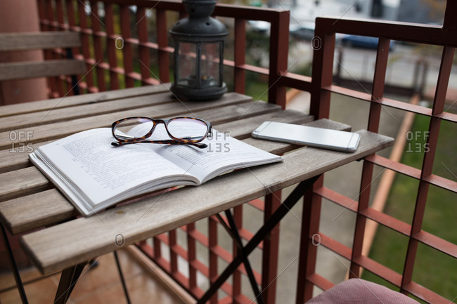 Book, glasses, smartphone and decorative lamp at wooden table