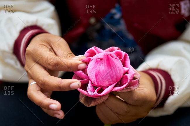 Detail of a woman folding a pink lotus flower