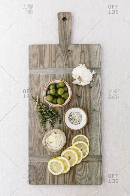 Ingredients for a savory meal, including garlic, salt, pepper, and olives