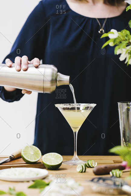 A woman is photographed as she is pouring martini in a glass