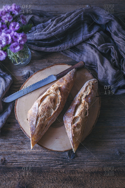 Sourdough baguette sliced in half on a rustic wooden table