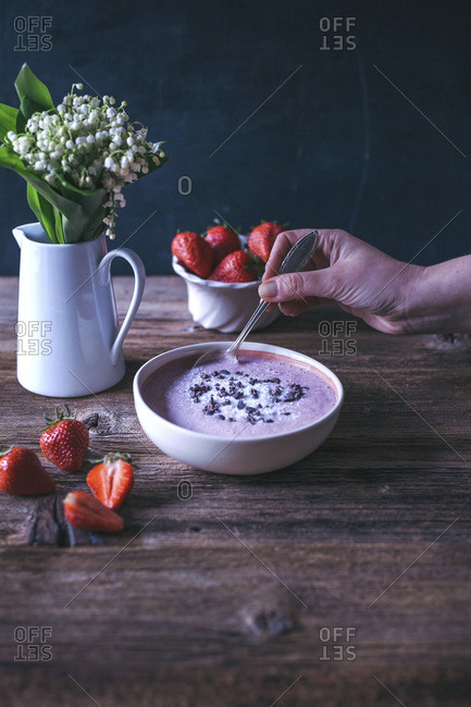 Woman eating strawberry banana smoothie bowl topped with coconut and cacao nibs