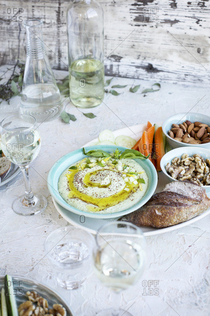 Meyer Lemon Basil Hummus served with vegetables, bread and white wine Photographed on a white plaster background
