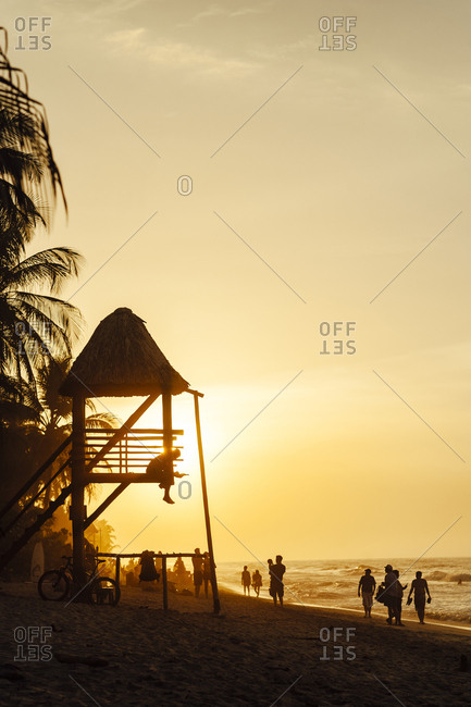 Wide view of people walking and a lifeguard tower at sunset