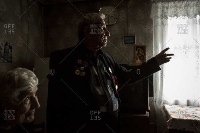 Gyumri, Armenia - March 11, 2016: Senior man standing in a window with his wife wearing medals from World War II
