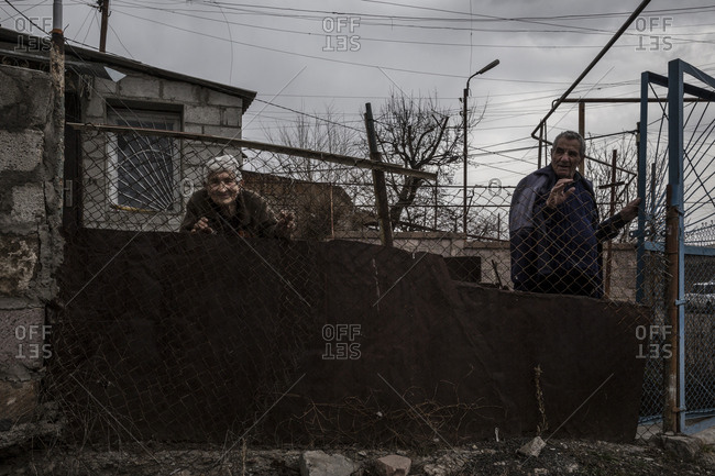 Gyumri, Armenia - March 11, 2016: Senior couple standing at a rusted fence outside their home