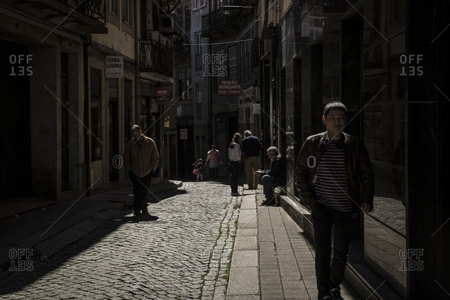 Porto, Portugal - April 23, 2016: People walking in a narrow cobblestone alley