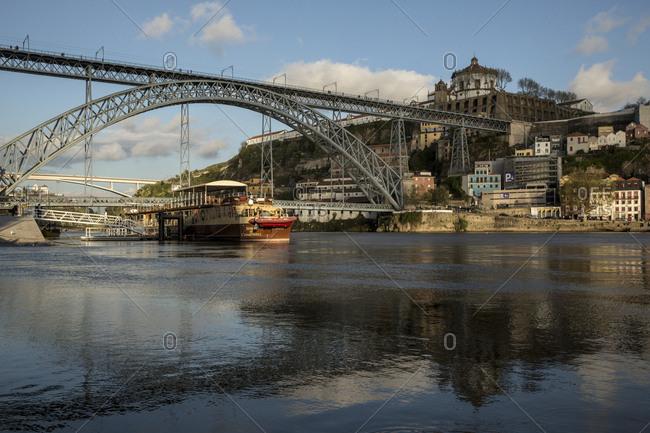 Porto, Portugal - April 23, 2016: River boat crossing the Douro under the Dom Luis bridge at dusk