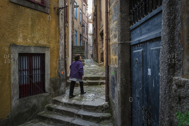 Porto, Portugal - April 23, 2016: Woman walking up steps in an alley between traditional buildings