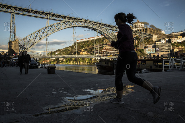 Porto, Portugal - April 23, 2016: Woman jogging on the waterfront near the Dom Luis bridge at dusk