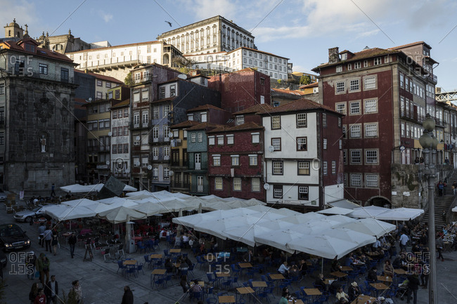 Porto, Portugal - April 23, 2016: Cafe tables and colorful buildings at the waterfront