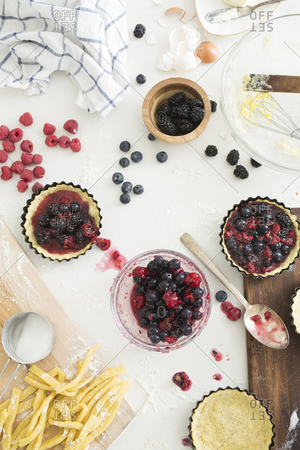 Ingredients for making tarts with freshly prepared mixed berries in tart tins