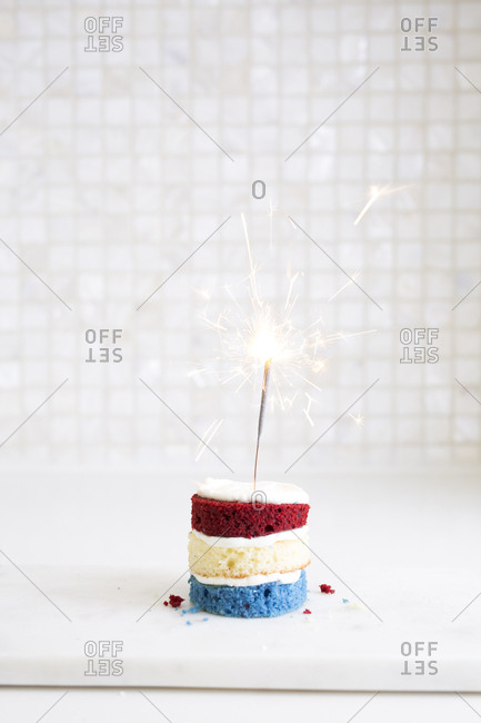 Small red, white, and blue cake with sparkler