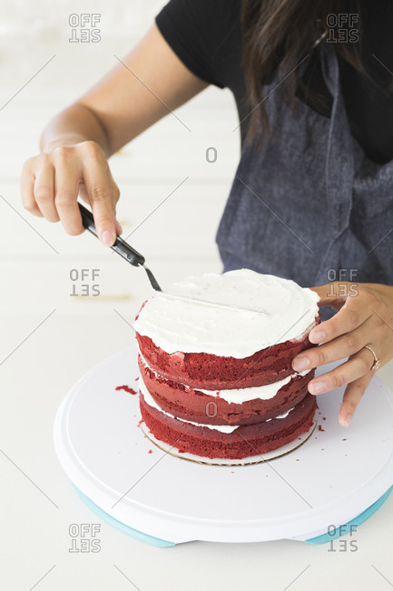 Baker frosting a red velvet cake with white icing