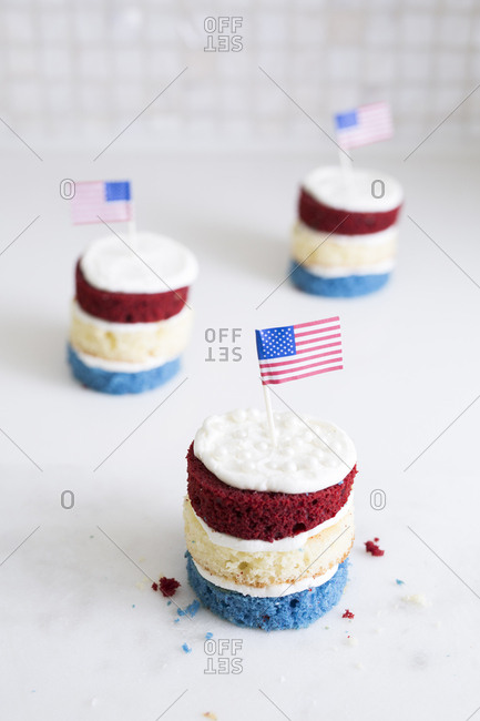 Three small red, white, and blue cakes with miniature American flags