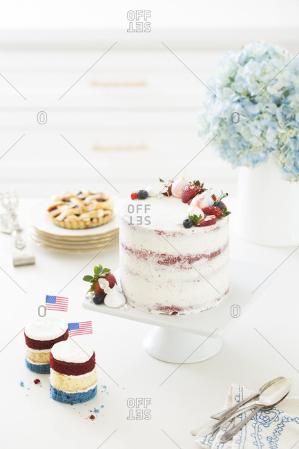 Small red, white, and blue cakes with miniature American flags served with a red velvet cake