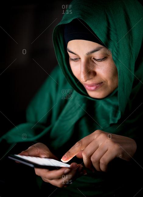 Happy Muslim woman using her phone