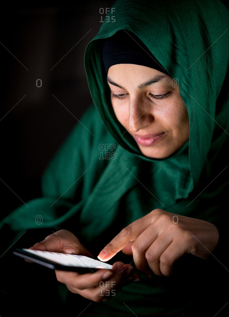 Happy Muslim woman using her phone
