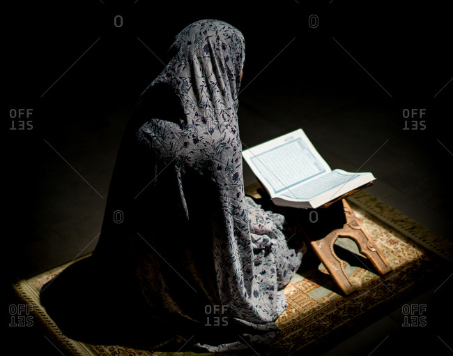 Muslim woman praying for god in dark room with Quran