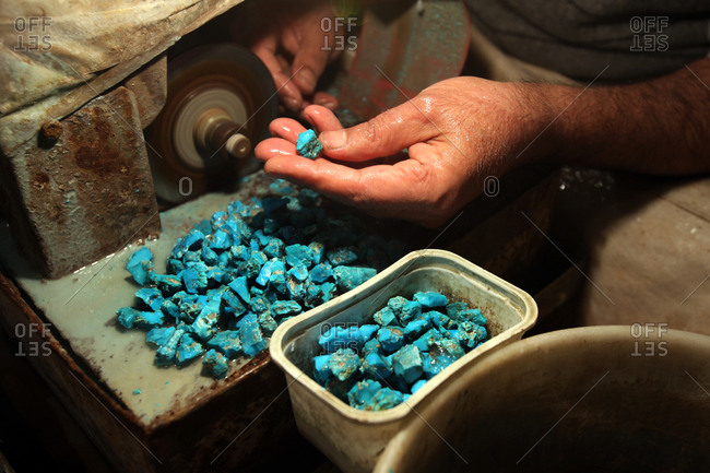 a man is working on turquoise