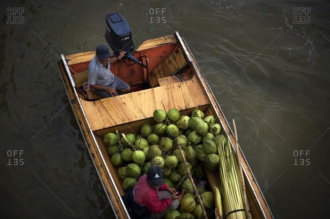 Brunei - July, 2011: A coconut seller on a boat seen on a river in Brunei