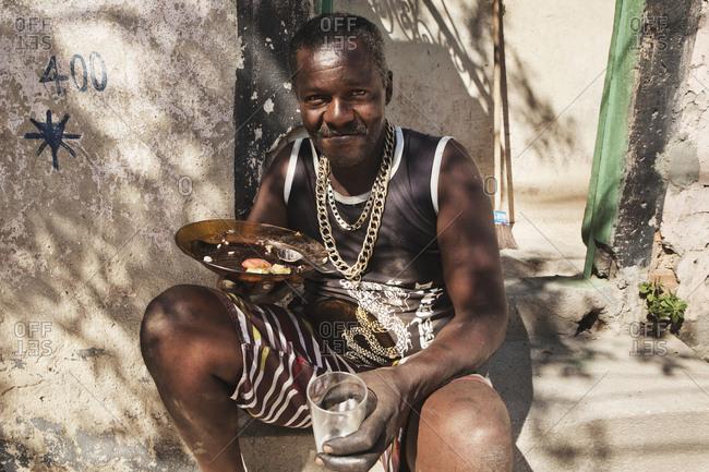 Rio de Janeiro, Brazil - October 13, 2013: A local man enjoys his meal in the sun in Cidade de Deus, which is located in the West Zone of Rio de Janeiro Cidade de Deus has become best known from the movie City of God