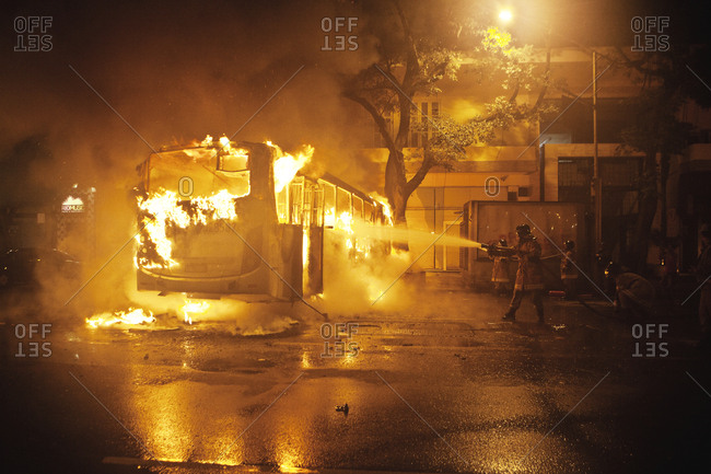 Rio de Janeiro, Brazil - October 8, 2013: Fire fighters try to extinguish a burning bus after a teacher's protest that turned into riots and violent clashes between protesters and police