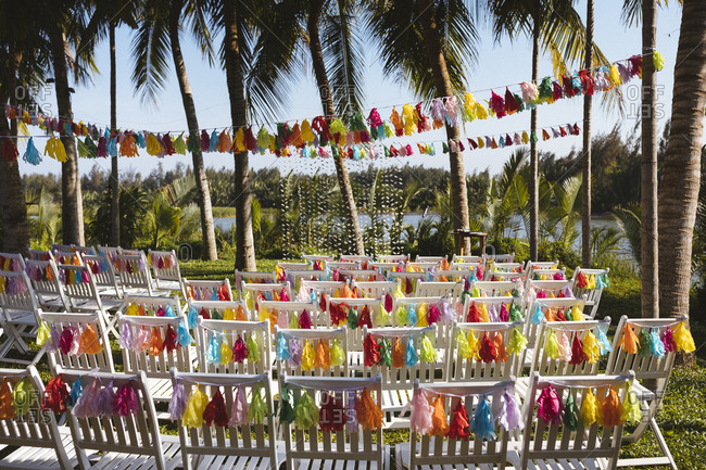 Colorful chair decor for a riverside garden wedding ceremony.