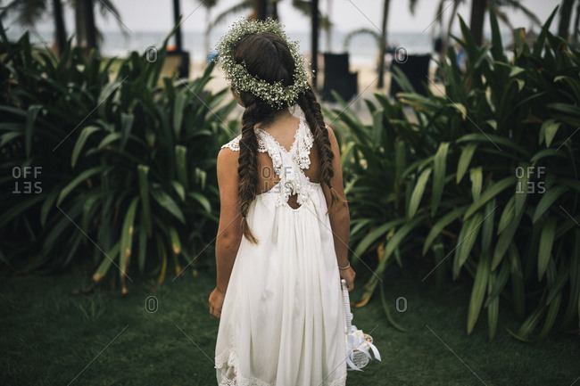 A young flower girl in a flower crown waits for a wedding ceremony to begin.