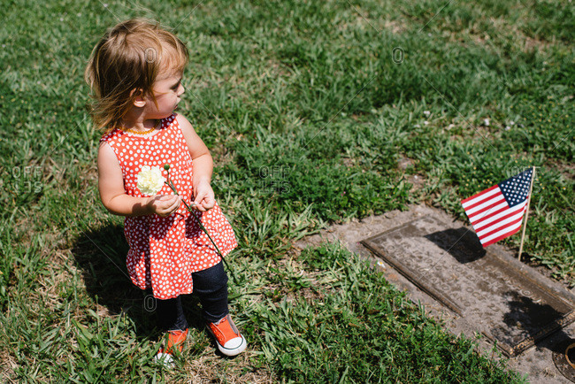 Toddler girl at cemetery on Memorial Day.