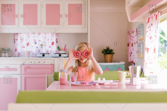 Girl covering her eyes with donuts