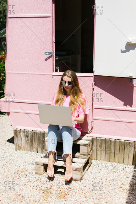 Woman with laptop outside a camper