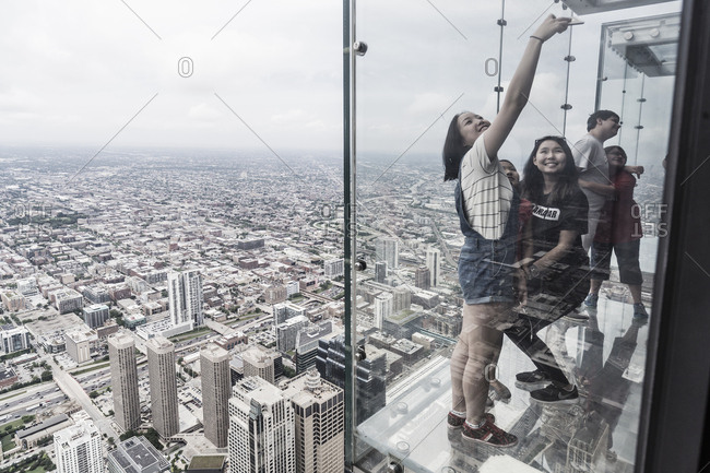 Chicago, Illinois - May 30, 2017: Downtown, Loop, Willis Tower, Sky deck, taking a selfie on the glass balcony suspended above the city