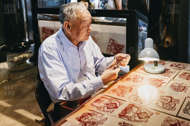 Guangzhou, China - April 29, 17: Asian senior man with Chinese paper-cut