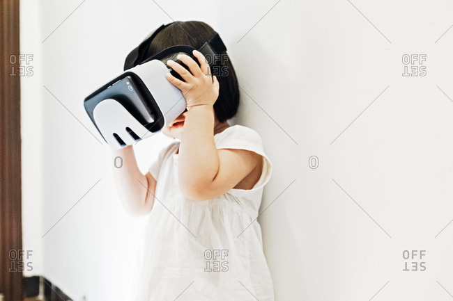 Asian little girl holding up virtual reality headset