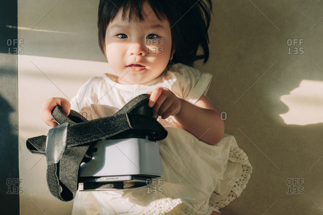 Asian little girl playing with virtual reality headset while laying on the floor