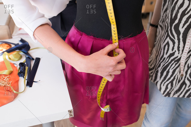 Clothes designers measuring mannequin