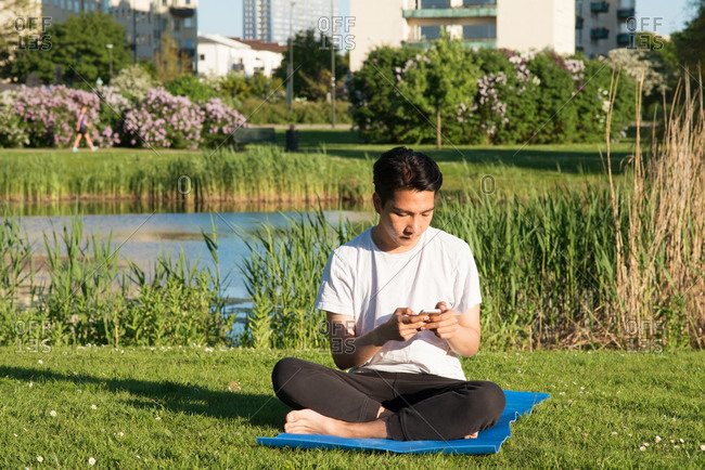 Man using his smartphone while sitting on a yoga mat in a park