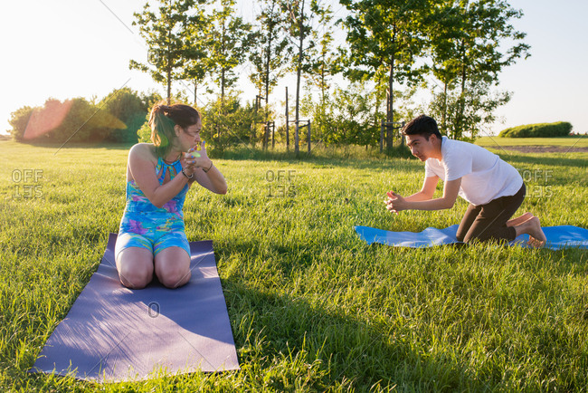 Two people practicing yoga outdoors